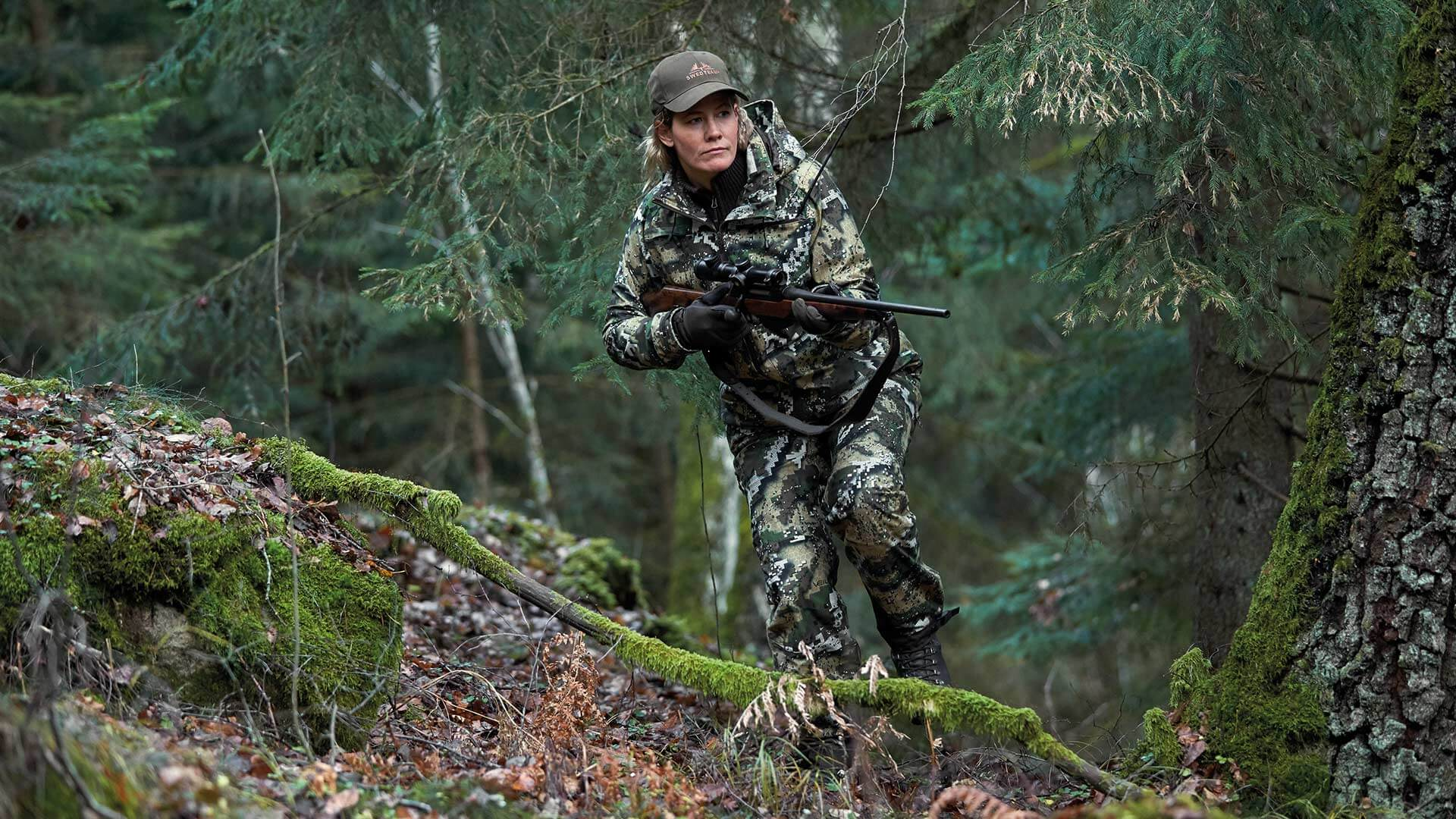 Hunter in brushy landscape dressed in camouflage clothes from DESOLVE®