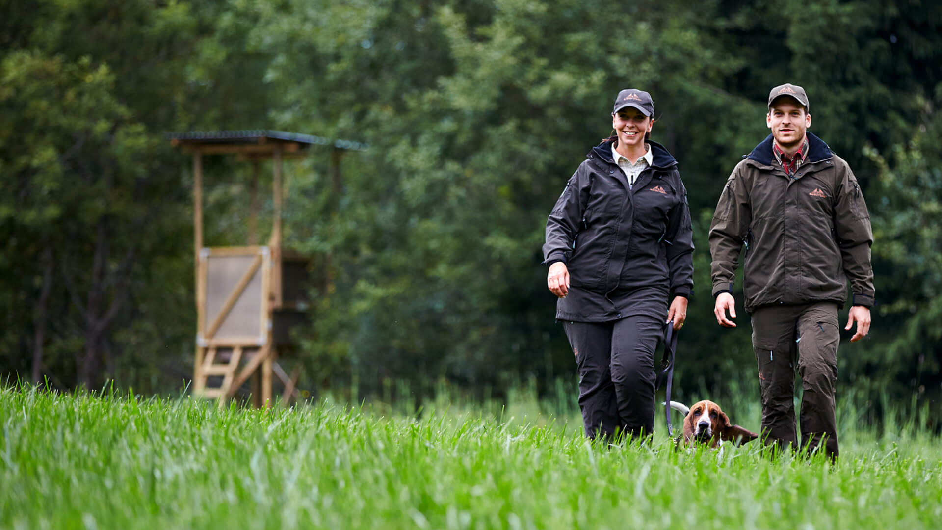 Hunters walking over meadow with dog, for small game hunting